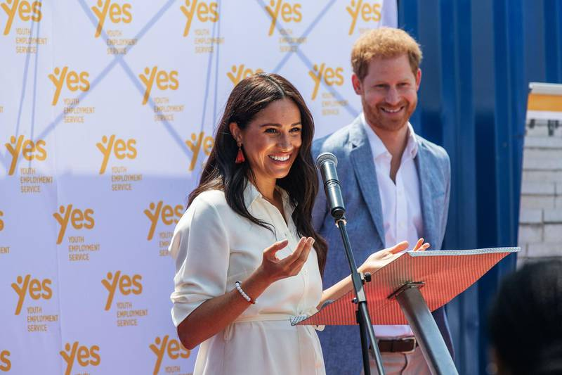 (FILES) In this file photo taken on October 2, 2019 Meghan, Duchess of Sussex (L), is watched by Britain's Prince Harry, Duke of Sussex (R) as she delivers a speech at the Youth Employment Services Hub in Tembisa township, Johannesburg.  Britain's Prince Harry and his wife Meghan handed out meals to sick people in Los Angeles, in their first known public activity since moving to California at the start of the state's coronavirus lockdown. The pair, who have formally stepped down as senior members of the British royal family, first volunteered with Project Angel Food last on April 12, 2020, delivering food to homes. / AFP / Michele Spatari