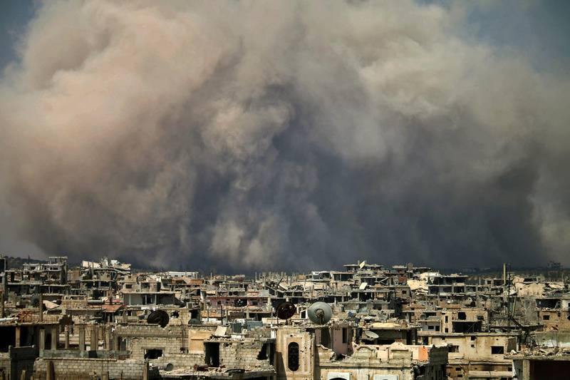 (FILES) In this file photo taken on August 8, 2017, smoke billows following a reported air strike on a rebel-held area in the southern Syrian city of Daraa. / AFP PHOTO / Mohamad ABAZEED