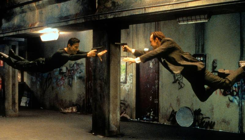 Keanu Reeves and Hugo Weaving pointing guns at each other in a scene from the film 'The Matrix', 1999. (Photo by Warner Brothers/Getty Images)