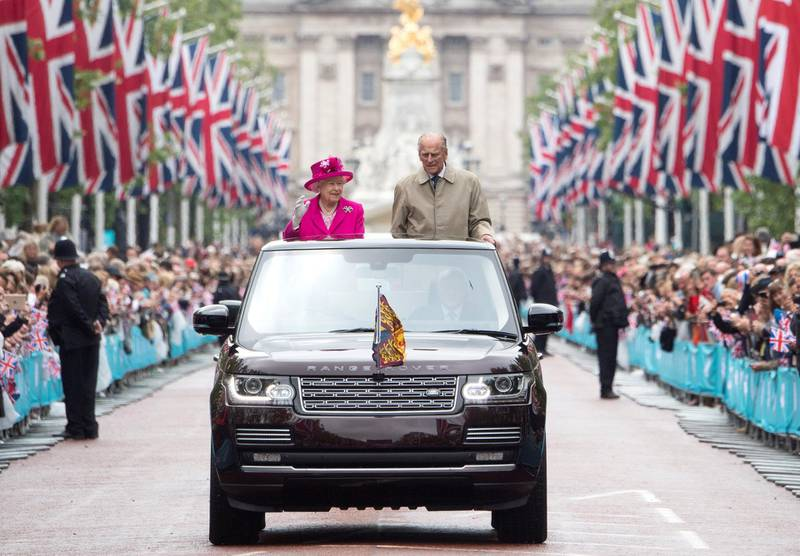 """LONDON, ENGLAND - JUNE 12: Queen Elizabeth II and Prince Philip, Duke of Edinburgh wave to guests attending """"The Patron's Lunch"""" celebrations for The Queen's 90th birthday on The Mall on June 12, 2016 in London, England. 10,000 guests have gathered on The Mall for a lunch to celebrate The Queen's Patronage of more than 600 charities and organisations. The lunch is part of a weekend of celebrations marking Queen Elizabeth II's 90th birthday and 63 year reign. The Duke of Edinburgh and other members of The Royal Family are also in attendance. During the lunch a carnival parade will travel down The Mall and around St James's Park.  (Photo by Arthur Edwards - WPA Pool/Getty Images)"""