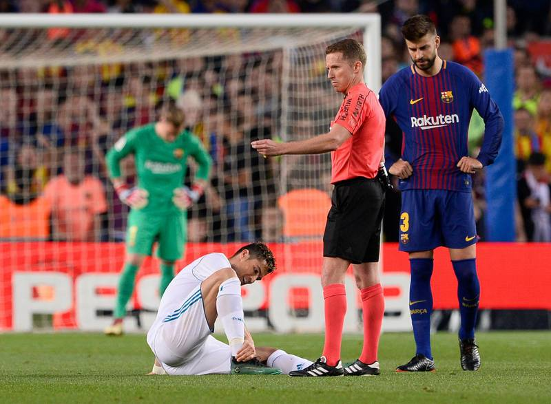 TOPSHOT - Real Madrid's Portuguese forward Cristiano Ronaldo (L) sits on the field after resulting injured dbeside Spanish referee Hernandez Hernandez (C) and Barcelona's Spanish defender Gerard Pique uring the Spanish league football match between FC Barcelona and Real Madrid CF at the Camp Nou stadium in Barcelona on May 6, 2018. / AFP PHOTO / Josep LAGO