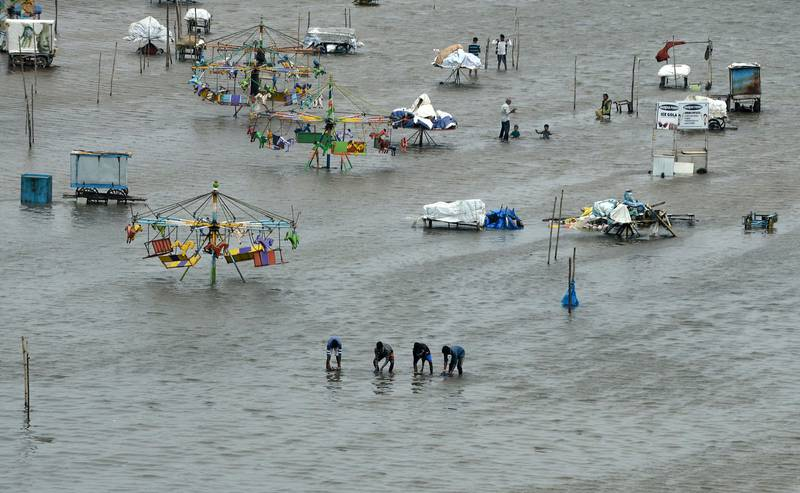 TOPSHOT - People walk through a flooded area of Marina Beach on the Bay of Bengal coast after heavy rains in Chennai on November 3, 2017. The arrival of the northeast monsoon in recent days has brought heavy rains to southern India's Tamil Nadu, submerging parts of the state capital Chennai. Devastating floods following the northeast monsoon in south India in November and December 2015 killed more than 500 people and displaced almost two million others.  / AFP PHOTO / ARUN SANKAR