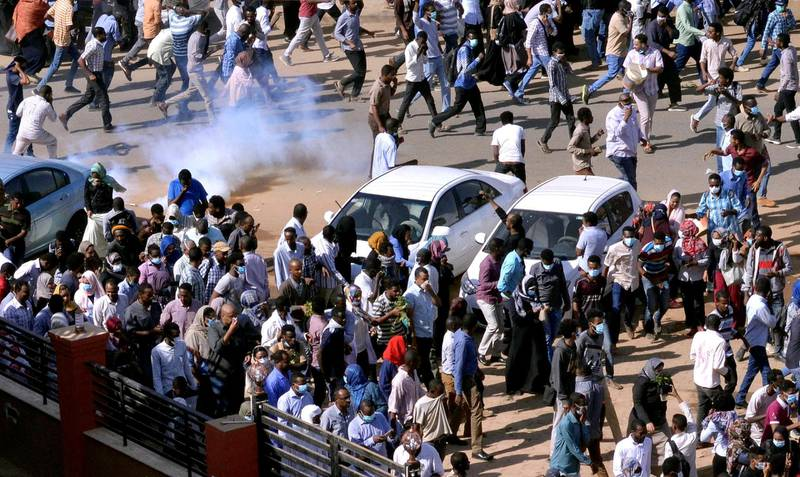 Sudanese demonstrators run from teargas lobbed to disperse them as they march along the street during anti-government protests in Khartoum, Sudan December 25, 2018. REUTERS/Mohamed Nureldin Abdallah