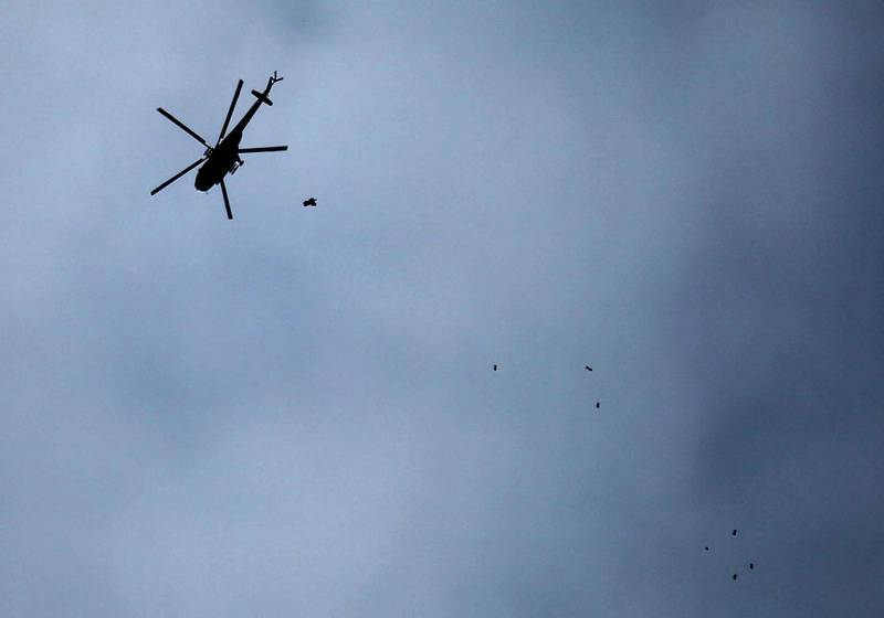 A picture taken on February 20, 2018 shows a Russian-made Syrian army attack helicopter dropping a payload over the rebel-held town of Arbin, in the besieged Eastern Ghouta region on the outskirts of the capital Damascus. / AFP PHOTO / Amer ALMOHIBANY