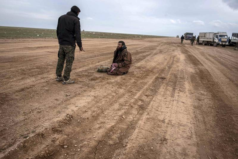 A suspected ISIS member is questioned by a member of the Syrian Democratic Forces outside Baghouz, Syria, 28 February 2019. Campbell MacDiarmid