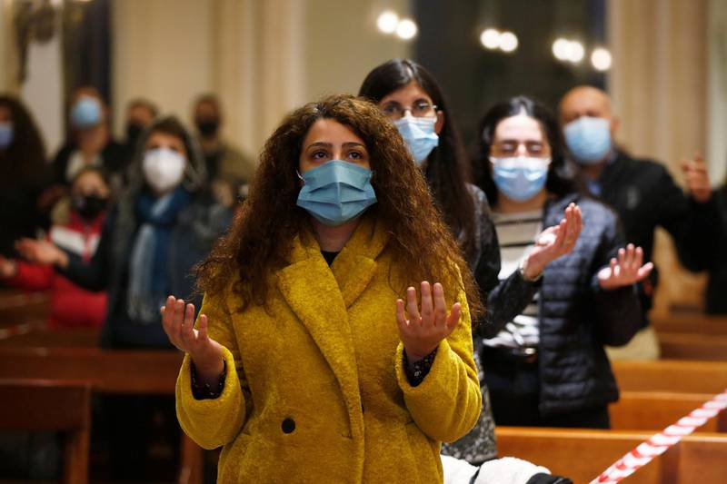 Faithfuls wearing protective masks and maintaining social distance attend a mass before turning on the lights on the Christmas tree, at Church of the Sacred Heart, amid fears over rising numbers of coronavirus disease (COVID-19) cases in downtown Amman, Jordan December 6, 2020. REUTERS/Muhammad Hamed