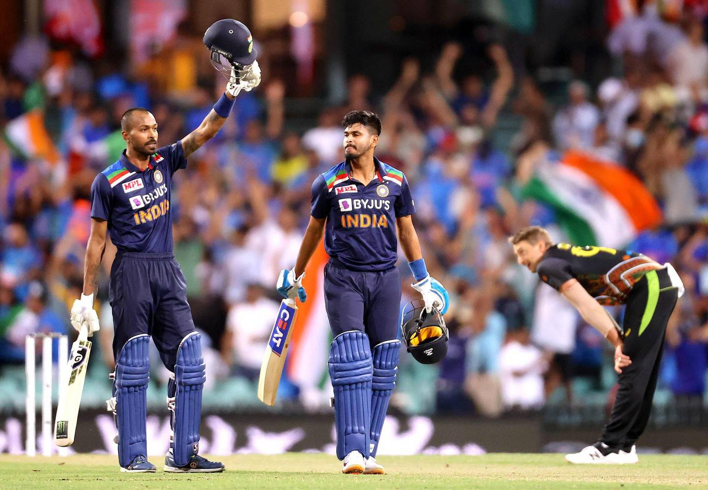 India's Hardik Pandya (L) and teammate Shreyas Iyer celebrate the victory as Australia's Daniel Sams (R) reacts during the second T20 cricket match between Australia and India at the Sydney Cricket Ground in Sydney on December 6, 2020.  / IMAGE RESTRICTED TO EDITORIAL USE - STRICTLY NO COMMERCIAL USE  / AFP / DAVID GRAY / / IMAGE RESTRICTED TO EDITORIAL USE - STRICTLY NO COMMERCIAL USE