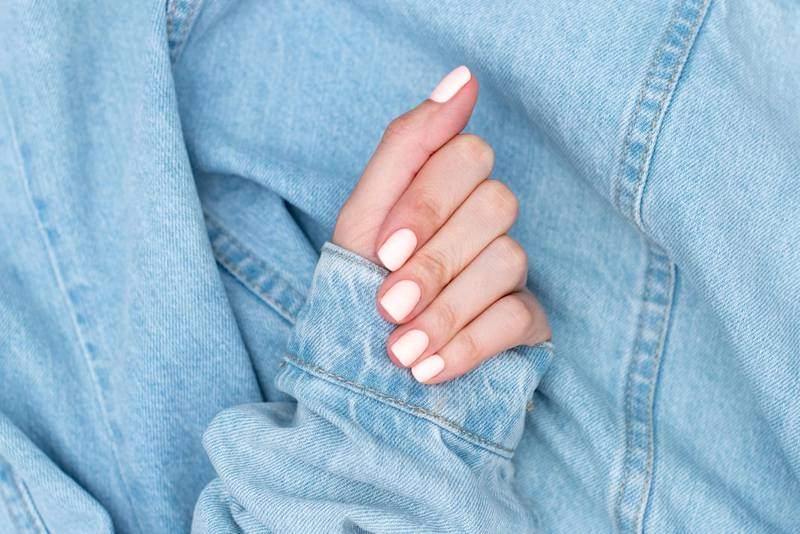 Bright neon red manicure on female hands on the background of jeans. Nail design. Beauty hands.