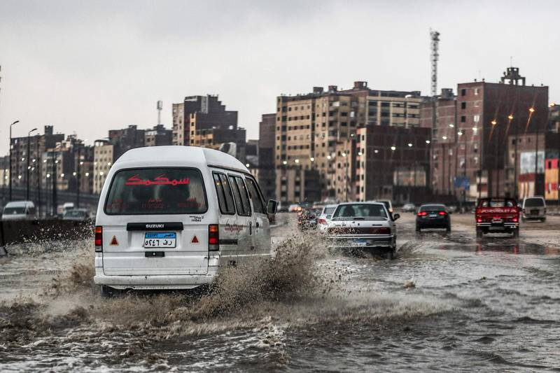 Vehicles drive along a flooded portion of the ring-road highway that encircles the Egyptian capital Cairo and it's twin city of Giza, in Giza on March 12, 2020, amdist a heavy rain storm.  / AFP / Mohamed el-Shahed