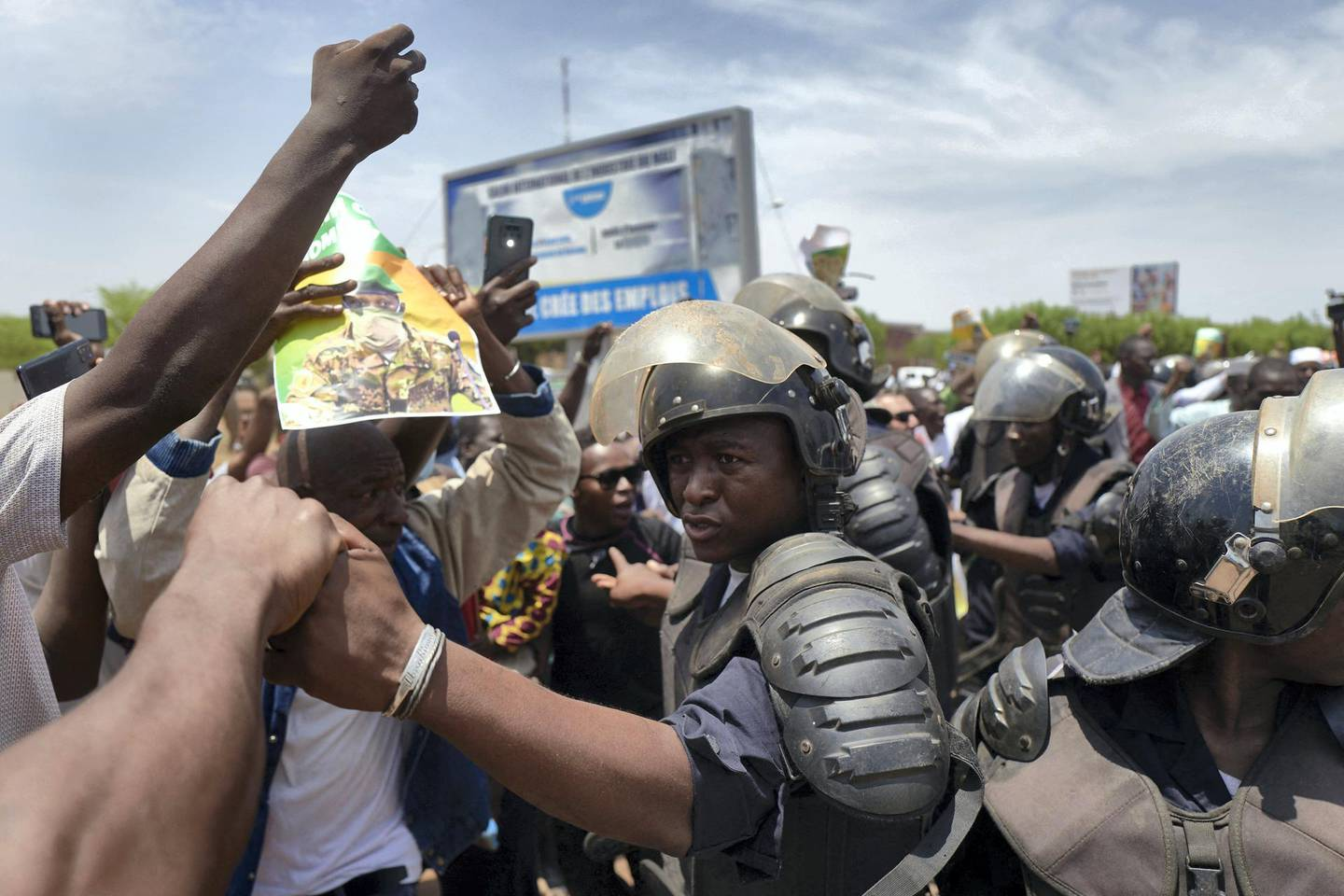 """Malian riot police keep supporters away from the vehicle of new President of Mali's transitional government Assimi Goita as he returns from Accra after a meeting with the ECOWAS (The Economic Community of West African States) representatives on May 31, 2021. - Malian strongman Colonel Assimi Goita returned home on Monday after West African leaders condemned a second coup that cemented his grip on power, calling on him to name a new prime minister but stopping short of reimposing sanctions.  At a crisis summit in Ghana on Sunday, the Economic Community of West African States (ECOWAS) decided to suspend Mali from the 15-nation bloc and urged Goita to appoint a new civilian premier and forge a new """"inclusive government"""" (Photo by Michele Cattani / AFP)"""