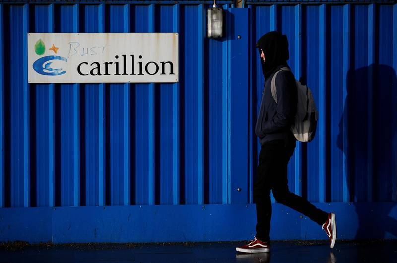 A person walks past defaced branding outside Carillion's Royal Liverpool Hospital site in Liverpool, Britain, January 16, 2018. REUTERS/Phil Noble