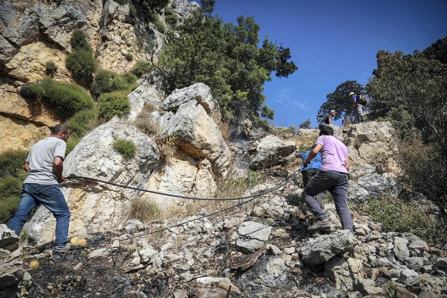 Volunteers climb to the site of a forest fire in  Jird Harar, in Lebanon's Akkar region on Aug. 30, 2020