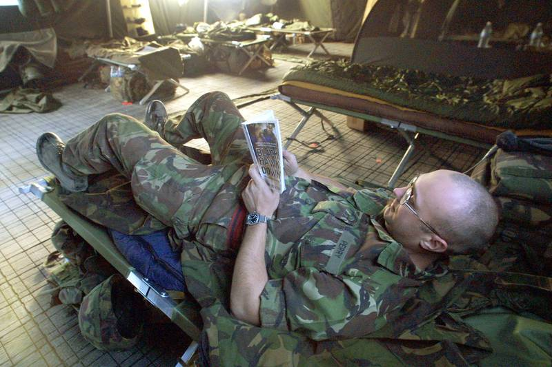 """400262 05: Fred Perry, a British Royal Engineer soldier, reads the book """"Black Hawk Down"""" inside his tent after a day of work January 29, 2002 at the International Security Assistance Force (ISAF) barracks at the Kabul airport in Kabul, Afghanistan. A United Nations mandated International Security and Assistance Force, made up of over 4, 000 foreign troops from 17 countries, regularly patrol the city, to improve security in the area. (Photo by Paula Bronstein/Getty Images)"""