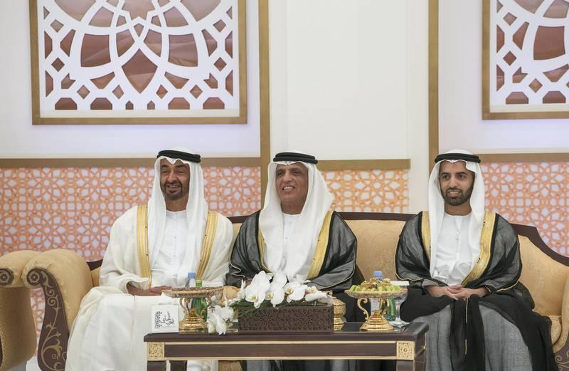 ADHAN, RAS AL KHAIMAH, UNITED ARAB EMIRATES - March 13, 2018: HH Sheikh Mohamed bin Zayed Al Nahyan, Crown Prince of Abu Dhabi and Deputy Supreme Commander of the UAE Armed Forces (L), attends a mass wedding reception for HH Sheikh Mohamed bin Saud bin Saqr Al Qasimi, Crown Prince and Deputy Ruler of Ras Al Khaimah (R), at Mohamed bin Zayed, Al Bayt Mitwahid wedding hall. Seen with HH Sheikh Saud bin Saqr Al Qasimi, UAE Supreme Council Member and Ruler of Ras Al Khaimah (C).  ( Mohamed Al Hammadi / Crown Prince Court - Abu Dhabi ) ---