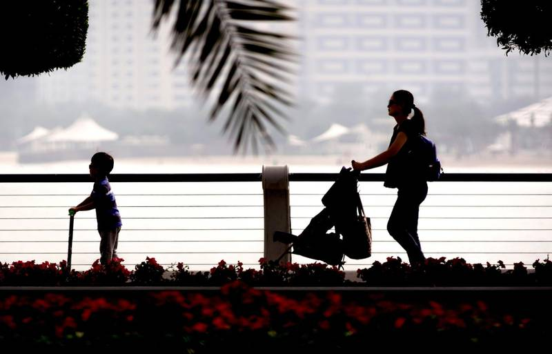 Abu Dhabi, United Arab Emirates, March 9, 2020. A mother and her children take a morning stroll at the Corniche, Abu Dhabi on a sunny but hazy day.   Victor Besa / The National