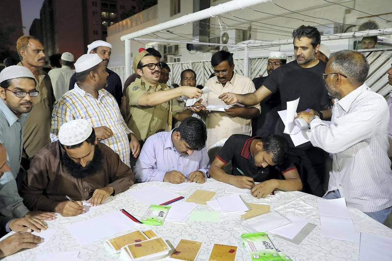 DUBAI , UNITED ARAB EMIRATES , JUNE 13 – 2018 :- Faraz Waqar ( postman ) member of the theatre group Goonj collecting letters from  labours during the iftar at Al Mehir Labour Camp in Al Quoz in Dubai. ( Pawan Singh / The National )  For News. Story by Anam Rizvi