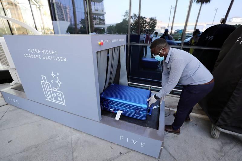 Dubai, United Arab Emirates - N/A. News. Coronavirus/Covid-19. A Five hotel employee puts luggage through a Ultra Violet sanitiser machine. Thursday, September 10th, 2020. Dubai. Chris Whiteoak / The National