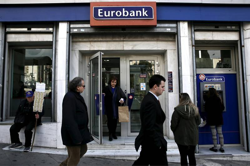 FILE PHOTO: People are seen in front of a Eurobank branch in Athens, Greece. March 19, 2015. REUTERS/Alkis Konstantinidis/File photo