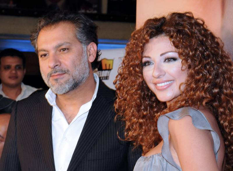 """Lebanese actress and singer Myriam Fares arrives with Syrian director Hatem Ali to a special screening of their new film """"Silina"""" at a movie theatre in the Egyptian capital Cairo late on May 13, 2009. The musical film is based on an operetta, titled """"Hala wal Malek"""" (Hala and the King), which was first presented in 1967 by Lebanese diva Fairuz and the Rahbani Brothers. AFP PHOTO/AMR AHMAD (Photo by AMR AHMAD / AFP)"""