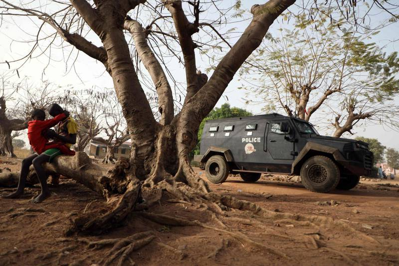 TOPSHOT - Children seen sitting a tree trunk next to an armoured personnel carrier is stationed inside the Government Science College where gunmen kidnapped dozens of students and staffs, in Kagara, Rafi Local Government Niger State, Nigeria on February 18, 2021 / AFP / Kola Sulaimon