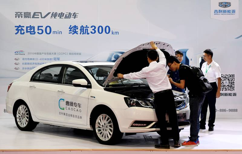 Men look at an electric vehicle of Caocao Zhuanche, a chauffeur ride-hailing platform backed by Zhejiang Geely Holding Group, at a new energy vehicle (NEV) trade fair in Zhengzhou, Henan province, China September 23, 2016. Picture taken September 23, 2016. REUTERS/Stringer  ATTENTION EDITORS - THIS IMAGE WAS PROVIDED BY A THIRD PARTY. CHINA OUT.