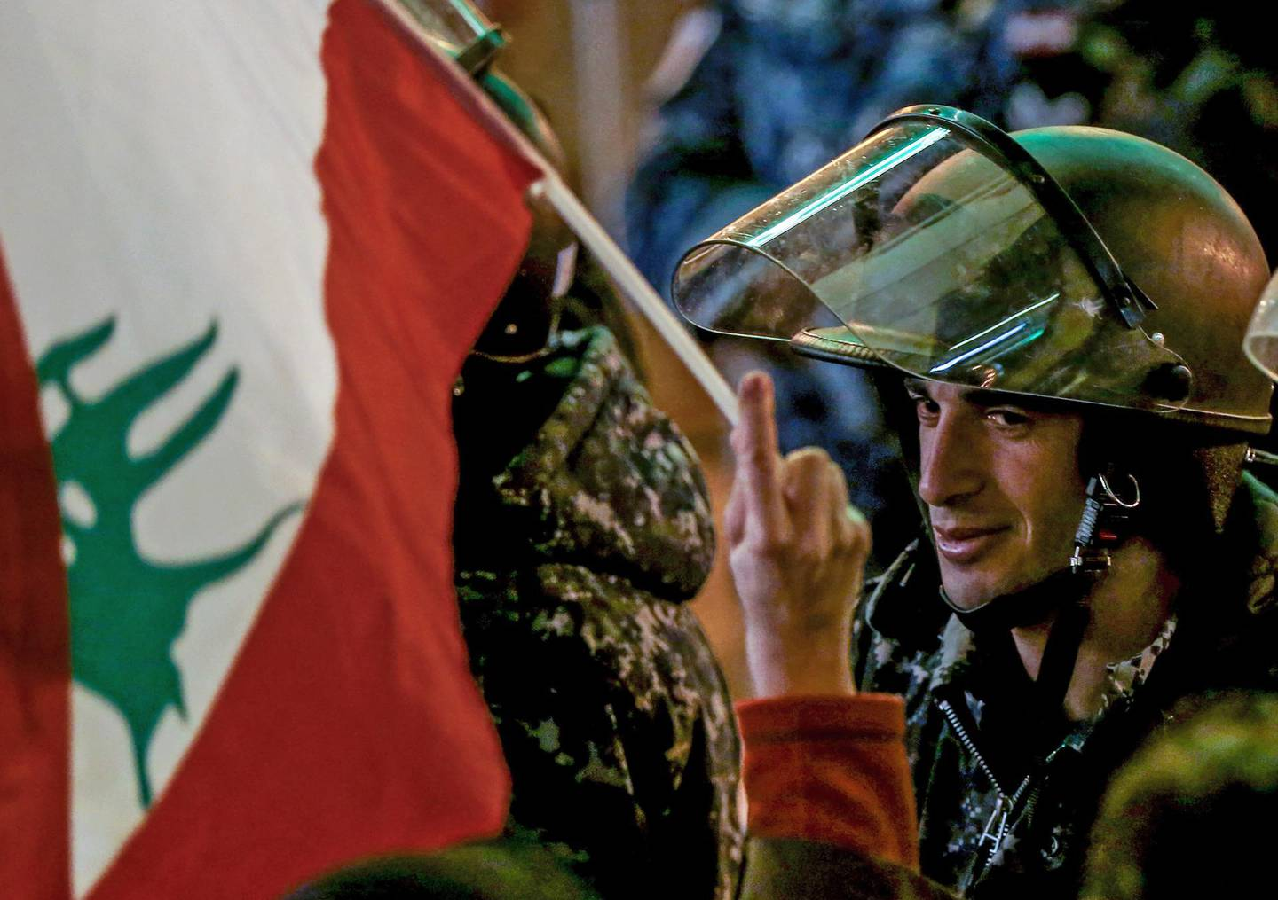 epa08055980 A protester waves the Lebanese flags in front of Lebanese policemen at a barricade, during an anti-government protest in front of the Parliament building in Beirut, Lebanon, 08 December 2019. Protests in Lebanon are continuing since it first erupted on 17 October, as protesters aim to apply pressure on the country's political leaders to over what they view as a lack of progress following the prime minister's resignation on 29 October,  demand to speed up the process to appointment of a new prime minister, without the corrupt political class. Lebanese President Michel Aoun called for formal consultations on 09 December with lawmakers to designate a new prime minister, but it was canceled after the candidate Samir Khatib announced his withdrawal from the candidacy, after his visit Dar Al Fatwa, as said to media that, the country's top Sunni religious authority told him the community supports resigned prime minister Saad Hariri to take back the post.  EPA/NABIL MOUNZER