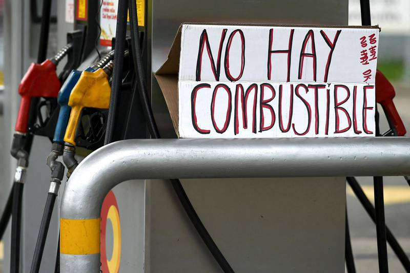 A sign reading 'No fuel' is seen at a closed gas station due to fuel shortages in Cali, Colombia, on May 4, 2021, following the clashes between demonstrators and riot police officers in the protests against the government's tax reform.  The international community on Tuesday decried what the UN described as an 'excessive use of force' by security officers in Colombia after official data showed 19 people were killed and 846 injured during days of anti-government protests. / AFP / LUIS ROBAYO