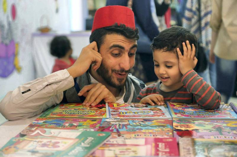 Storyteller Mohammed Al-Amoudi with children at a Gaza book exhibition.