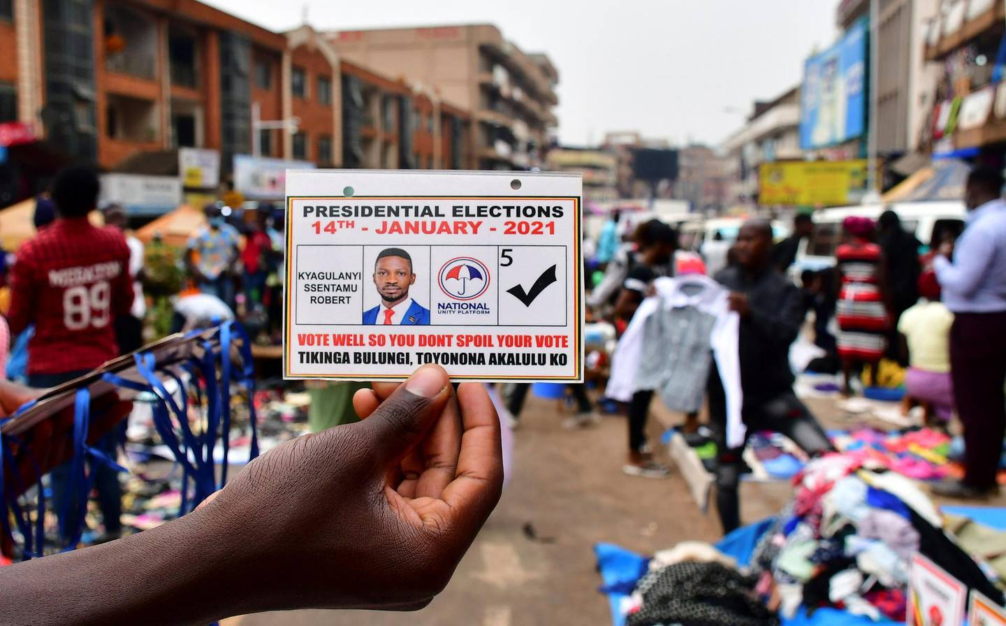 A vendor holds an electoral card of Ugandan opposition Presidential candidate Robert Kyagulanyi also known as Bobi Wine ahead of the presidential and parliamentary elections, in Kampala, Uganda January 12, 2021. REUTERS/Abubaker Lubowa