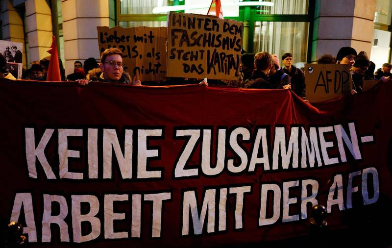 """A protestor holds up a banner which reads """"No cooperation with the AFD"""" during a rally outside the heahquaters of the Free Democratic Party (FDP) in Berlin on February 5, 2020. The tiny central state of Thuringia broke a German political taboo when a candidate for the regional premiership was unexpectedly heaved into office with  the help from the far-right AfD party. Thomas Kemmerich, a politician from the economically liberal Free Democratic Party (FDP), scored 45 votes, leapfrogging incumbent Bodo Ramelow of the Left party by one vote.    / AFP / John MACDOUGALL"""