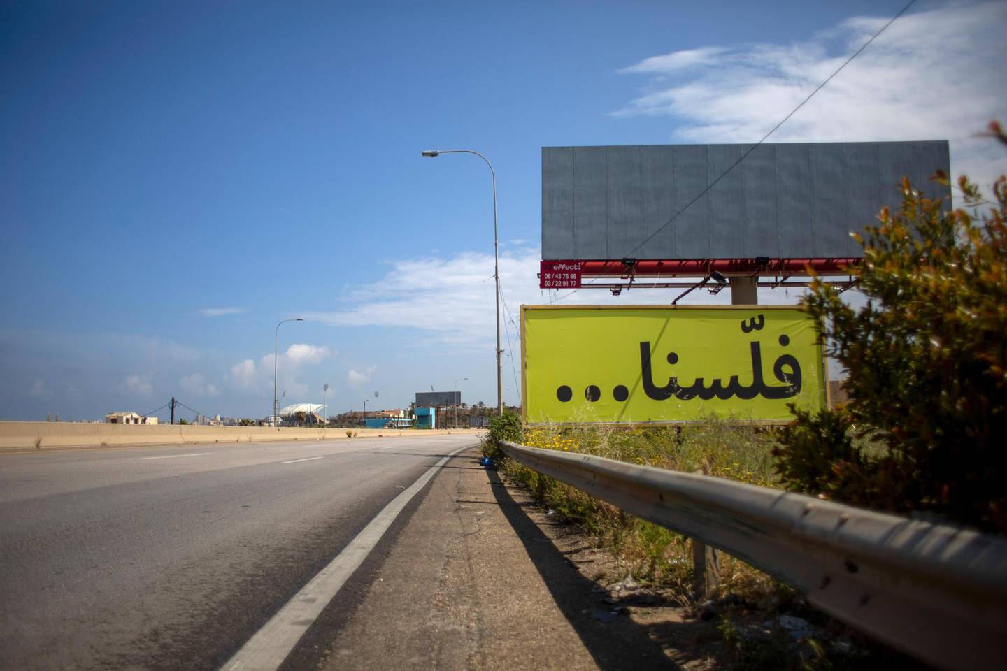 """FILE - In this Tuesday, May 5, 2020 file photo, a billboard with Arabic that reads, """"We are broke, is displayed on an empty major highway that links the capital Beirut to the northern city of Tripoli, Lebanon. Lebanon's government agreed Tuesday, July 21, 2020  to hire a New York-based company to conduct a forensic audit of the country's central bank accounts to determine how massive amounts of money were spent in the nation plagued by corruption. (AP Photo/Hassan Ammar, File)"""