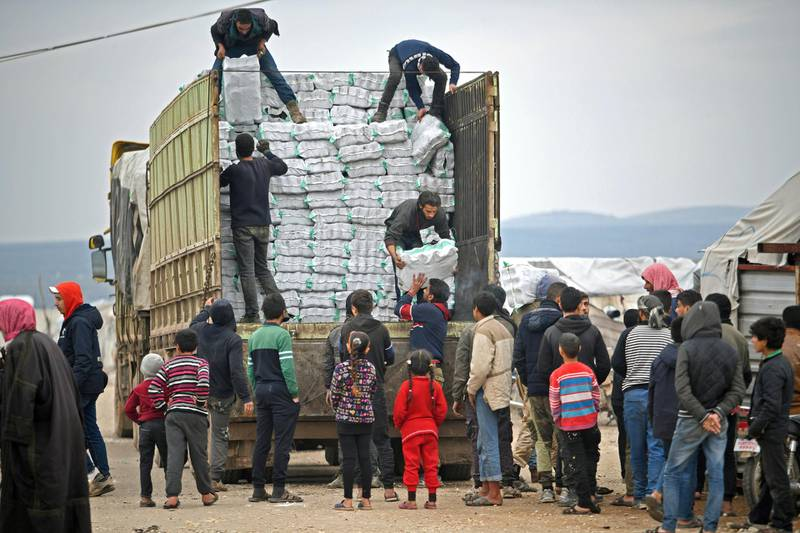 Displaced Syrians queue to receive humanitarian aid, consisting of heating material and drinking water, at a camp in the town of Mehmediye, near the town of Deir al-Ballut along the border with Turkey, on February 21, 2020. (Photo by Rami al SAYED / AFP)