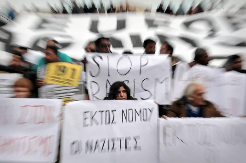 Demonstrators hold placards during a march for democracy, against racism, antisemitism and neo-Nazism in front of the greek Parliament in Athens, on December 15, 2012.    AFP PHOTO / LOUISA GOULIAMAKI (Photo by LOUISA GOULIAMAKI / AFP)