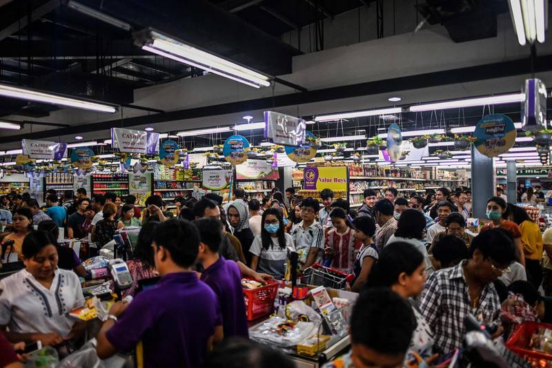This photo taken on March 12, 2020 shows people panic buying groceries in a supermarket, after hearing rumours related to the COVID-19 coronavirus, in Yangon. Shelves are being stripped bare of toilet rolls, hand sanitiser and surgical masks everywhere from Japan to France to the United States as panic buying criss-crosses the globe with the coronavirus, defying repeated calls for calm and disrupting supply chains. / AFP / Ye Aung THU