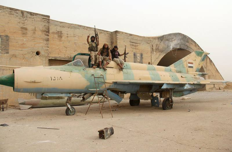 Members of Al-Qaeda's Syrian affiliate and its allies sit on top of a former Syrian army MiG-21 figther jet after they seized the Abu Duhur military airport, the last regime-held military base in northwestern Idlib province on September 9, 2015 in the latest setback for President Bashar al-Assad's forces. Al-Nusra Front and a coalition of mostly Islamist groups captured the military airport after a siege that lasted two years, the Syrian Observatory for Human Rights monitor said. AFP PHOTO / OMAR HAJ KADOUR (Photo by OMAR HAJ KADOUR / AFP)