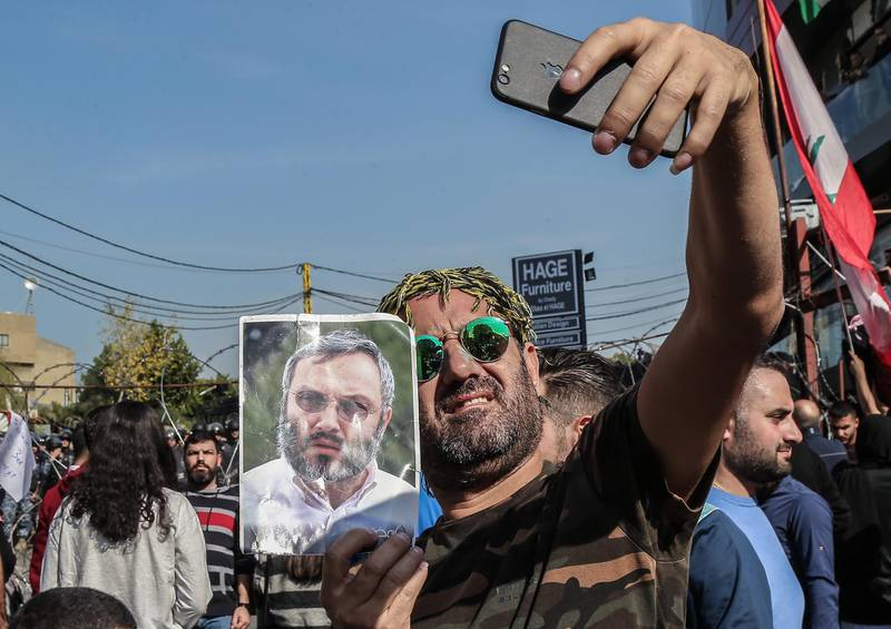 epa08022041 A protester holds a picture of late Hezbollah commander Imad Munghnyeh as he takes a selfie during a protest against the US policy next to the US Embassy at Awkar north of Beirut, Lebanon, 24 November 2019. Protests in Lebanon are continuing since first erupted on 17 October, as protesters aim to apply pressure on the country's political leaders over what they view as a lack of progress following the resignation of Prime Minister Saad Hariri on 29 October.  EPA/NABIL MOUNZER