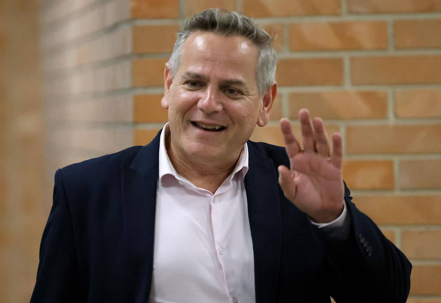"""Israeli politician Nitzan Horowitz of the Meretz party waves as he arrives to attend a parliamentary meeting at the Knesset in Jerusalem, ahead of a vote on a new government, on June 13, 2021. Israel's Prime Minister Benjamin Netanyahu faces the likely end of his 12-year reign ahead of a parliament vote in which a fragile """"change"""" coalition hopes to oust him and form a new government. / AFP / Gil COHEN-MAGEN"""