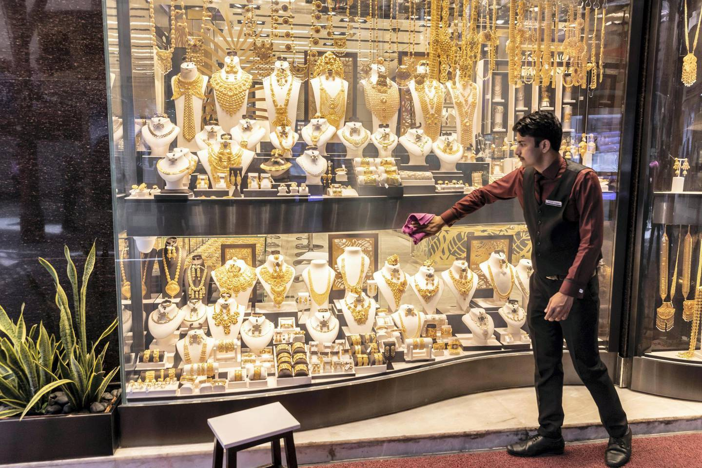 DUBAI, UNITED ARAB EMIRATES.  02 JULY 2018. The Gold Souk in Deira is due for an upgrade by the Munisipality. A man cleans a shop front window displaying gold jewellery. (Photo: Antonie Robertson/The National) Journalist: Anam Rizvi. Section: National.