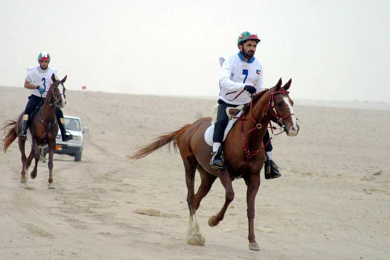 Dubai Crown Prince Sheikh Mohammed bin Rashed al-Maktum (R) and his son Sheikh Hamdan take part 04 December 2003 in the Horses Capacity and Endurance Championship in Kuwait City. Many well-known jockeys from the United Arab Emirates and Kuwait are competing in the event.     AFP PHOTO/Yasser AL-ZAYYAT (Photo by YASSER AL-ZAYYAT / AFP)