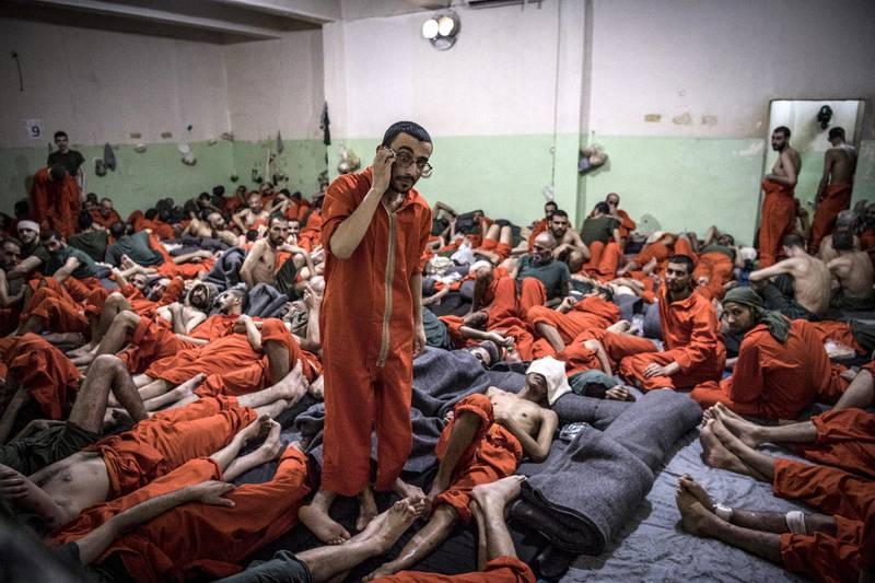 Men, suspected of being affiliated with the Islamic State (IS) group, gather in a prison cell in the northeastern Syrian city of Hasakeh on October 26, 2019. - Kurdish sources say around 12,000 IS fighters including Syrians, Iraqis as well as foreigners from 54 countries are being held in Kurdish-run prisons in northern Syria. (Photo by FADEL SENNA / AFP)