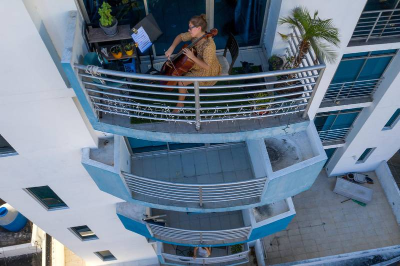 This picture taken on March 23, 2020 shows Uruguayan cellist Karina Nunez playing on the balcony of her apartment in Panama City, during the mandatory isolation from 5pm to 5am as a preventive measure against the spread of the COVID-19 novel coronavirus. - Over a 24-hour period, in a world where a third of humanity is now under orders to stay home, AFP photographers have captured snapshots of daily life during the coronavirus pandemic. (Photo by Luis ACOSTA / AFP)