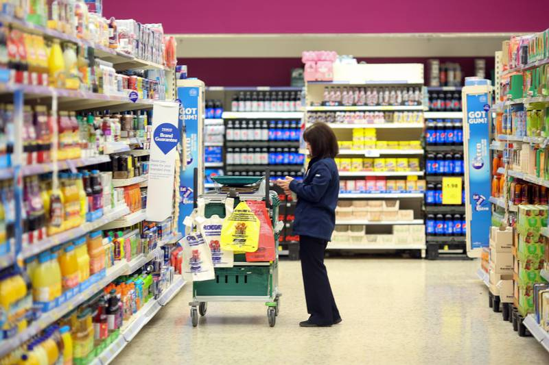 An employee selects items of shopping for home delivery at the Tesco Basildon Pitsea Extra supermarket, operated by Tesco Plc, in Basildon, U.K., on Tuesday, Dec. 1, 2015. Many European food retailers are coming to terms with persistently low inflation as well as consumers who remain frugal yet purchase food more frequently. Photographer: Chris Ratcliffe/Bloomberg