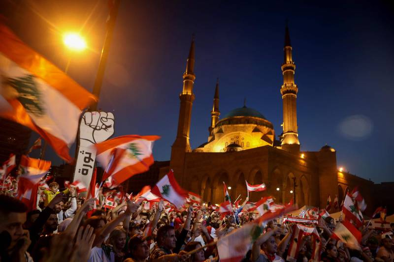 TOPSHOT - Lebanese anti-government protesters wave the national flag during a demonstration in downtown Beirut on November 17, 2019. Thousands of Lebanese took to the streets today, as an unprecedented protest movement which took off on October 17 against the ruling elite deemed corrupt, entered its second month with the country gripped in political and economic uncertainty. / AFP / Patrick BAZ
