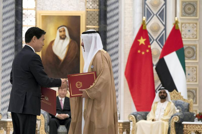 ABU DHABI, UNITED ARAB EMIRATES - July 20, 2018:  HE Sultan bin Saeed Al Mansouri, UAE Minister of Economy (R), exchanges an MOU with a member of the Chinese delegation, at the Presidential Palace. Witnessed by HH Sheikh Mohamed bin Rashid Al Maktoum, Vice-President, Prime Minister of the UAE, Ruler of Dubai and Minister of Defence (back R) and HE Xi Jinping, President of China (back L),  ( Mohamed Al Hammadi / Crown Prince Court - Abu Dhabi ) ---