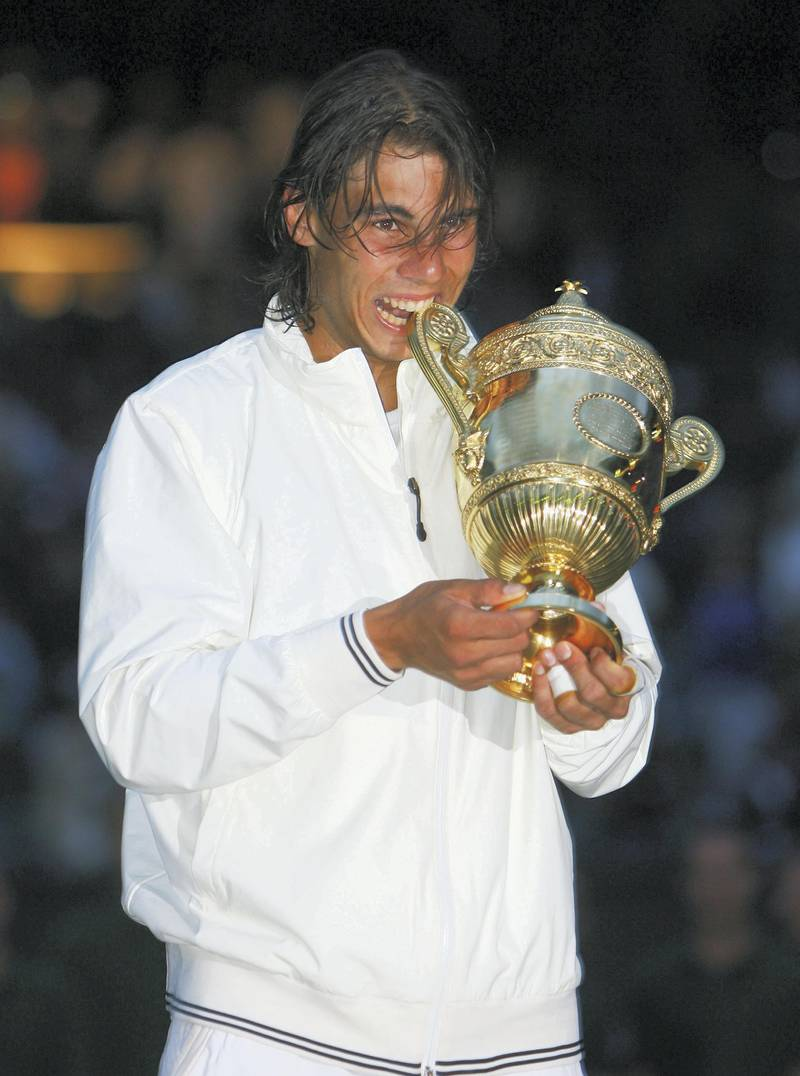 LONDON - JULY 06:  Rafael Nadal of Spain celebrates with the trophy winning the Championship during the men's singles Final match against Roger Federer of Switzerland on day thirteen of the Wimbledon Lawn Tennis Championships at the All England Lawn Tennis and Croquet Club on July 6, 2008 in London, England.  (Photo by Clive Brunskill/Getty Images)