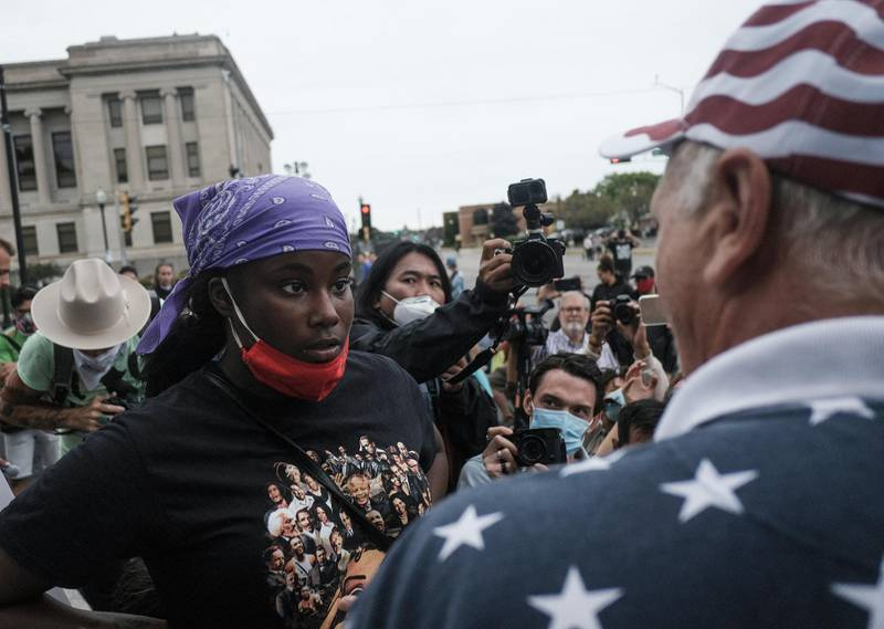 A demonstrator, left, and a supporter of U.S. President Donald Trump, right, engage in verbal arguments near Civic Center Park in Kenosha, Wisconsin, U.S., on Tuesday, Sept. 1, 2020. Donald Trump lauded police and National Guard members in Kenosha, Wisconsin, on Tuesday, where the shooting of a Black man by police last month has reignited national protests against racial inequality and street violence the president has sought to blame on Democrats. Photographer: Matthew Hatcher/Bloomberg