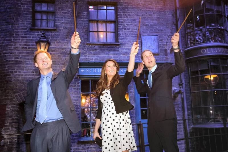 LONDON, ENGLAND - APRIL 26:  Prince Harry, Catherine, Duchess of Cambridge and Prince William, Duke of Cambridge raise their wands on the set used to depict Diagon Alley in the Harry Potter Films during the Inauguration Of Warner Bros. Studios Leavesden on April 26, 2013 in London, England.  (Photo by Paul Rogers - WPA Pool/Getty Images)
