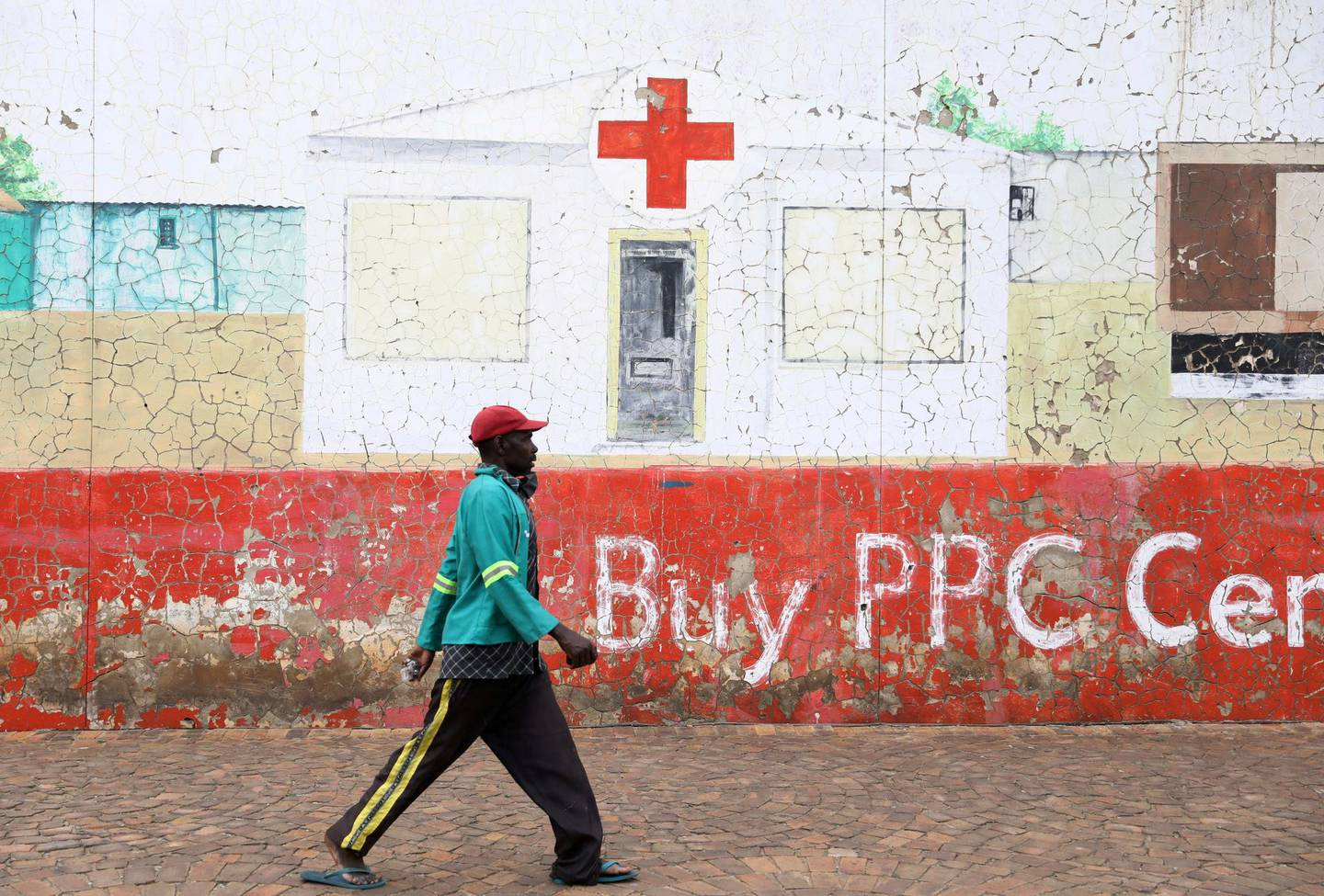 FILE PHOTO: A man walks beneath a mural depicting a hospital in Soweto, South Africa, December 28, 2020. REUTERS/Siphiwe Sibeko/File Photo