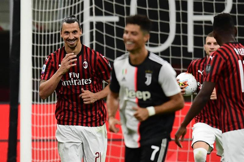AC Milan's Swedish forward Zlatan Ibrahimovic (L) reacts next to Juventus' Portuguese forward Cristiano Ronaldo (C) after scoring a penalty during the Italian Serie A football match AC Milan vs Juventus played behind closed doors on July 7, 2020 at the San Siro stadium in Milan, as the country eases its lockdown aimed at curbing the spread of the COVID-19 infection, caused by the novel coronavirus.  / AFP / Miguel MEDINA