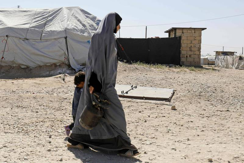 A woman walks with a child at a camp for Islamic State (IS) group-affiliated people in the northern Syrian village of Malikiya near the border with Turkey on September 29, 2018. Syria's Kurds are holding hundreds of alleged foreign fighters from the Islamic State group, but say they will not try them and have urged their home countries to repatriate them. / AFP / Delil souleiman